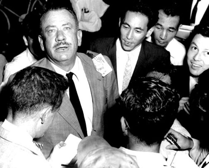 Image of John Steinbeck with reporters at 1957 PEN conference in Tokyo